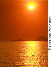 people swim in sea against sun in red sky above sea islands