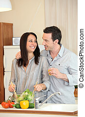 perfect housewife preparing meal with husband by her side