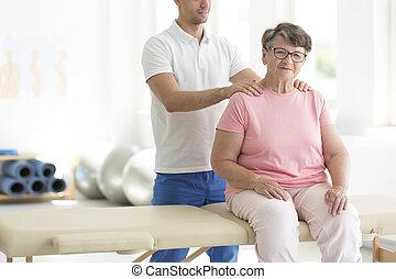 Personal masseur massaging senior woman