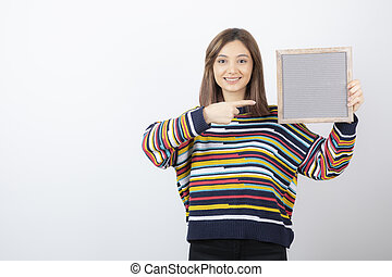 Photo of a young girl model standing and pointing at a frame