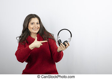 Photo of a young woman in red sweater pointing at headphones