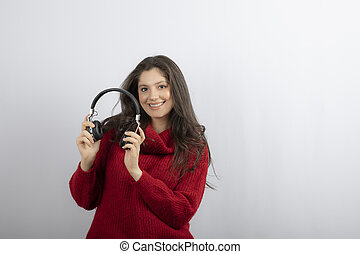 Photo of a young woman in red sweater taking off headphones
