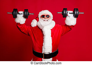 Photo of pensioner old man white beard lift heavy dumbbells smiling leave youngsters behind close strength competition win wear santa costume sunglass headwear isolated red color background