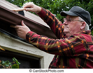 senior male cleaning out gutter outside house
