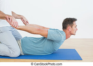 Side view of a physical therapist assisting young man with stretching exercises in the gym hospital