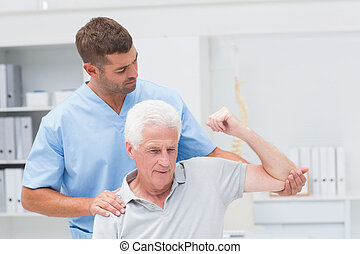Physiotherapist giving physical therapy to senior man in clinic