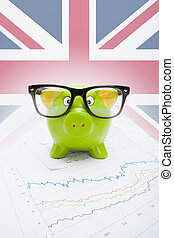 Piggy bank over stock market chart with British flag on background - part of series