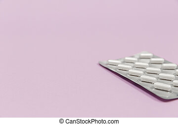 Pills in blister packs on a pink background