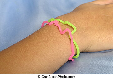 Pink and green Bracelets bandz with animals forms on child wrist, with blue background