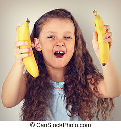 Playful laughing happy long hair kid girl holding and showing yellow bright bananas. Toned vintage portrait