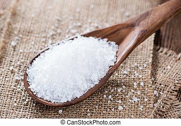 Portion of Salt on dark wooden background (close-up shot)