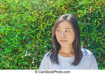 Portrait Asian woman wearing whit t-shirt and thinking something. She looking at right side hand with green bush in the background.