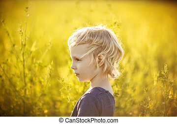 Portrait of a four-year-old blonde girl in a field with yellow flowers