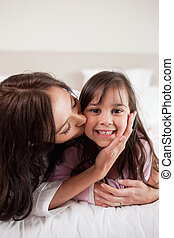 Portrait of a mother kissing her daughter