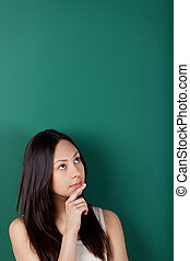 pensive young woman against blackboard