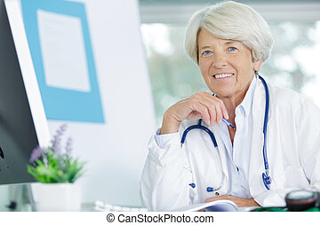 portrait of a senior woman doctor in her office