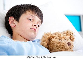 Portrait of a sick boy lying in a hospital bed