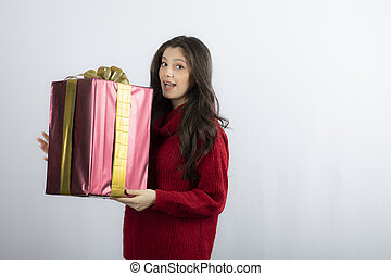 Portrait of a smiling girl in sweater holding present box