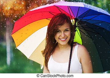 Portrait of beautiful and smiling woman with umbrella