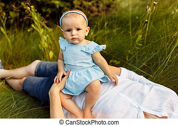 Portrait of beautiful baby girl in daddy's arms at the park