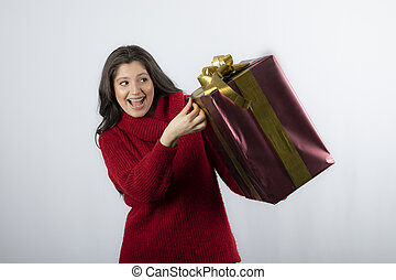 Portrait of beautiful smiling woman in red sweater holding Christmas gift box