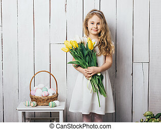 Portrait of cheerful little blonde girl with tulips bouquet on white wood background