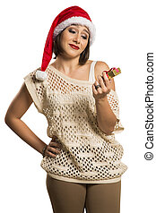 Portrait of disappointed young woman holding Christmas gift in white background.