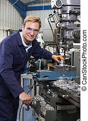 Portrait Of Engineer Using Drill In Factory