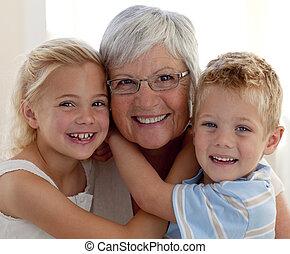 Portrait of smiling grandmother and grandchildren hugging