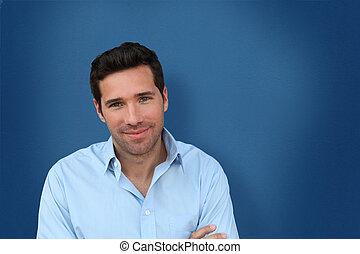 Portrait of handsome man standing on blue background