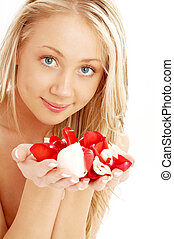 happy blond in spa with red and white rose petals