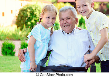 Portrait of happy old grandfather and cute children