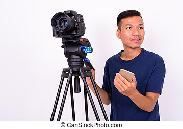 Portrait of happy young Asian man with camera using phone