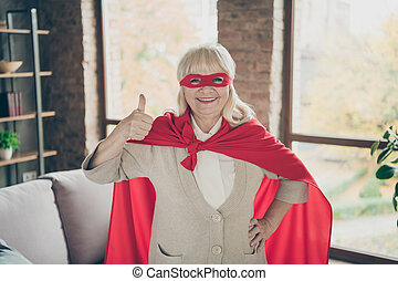 Portrait of her she nice attractive glad cheerful cheery gray-haired lady wearing red costume super granny showing thumbup excellent service at industrial brick loft modern style interior house