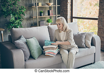 Portrait of her she nice attractive kind hardworking gray-haired granny sitting on divan folding belongings things clothing duty at industrial brick loft modern style interior house apartment