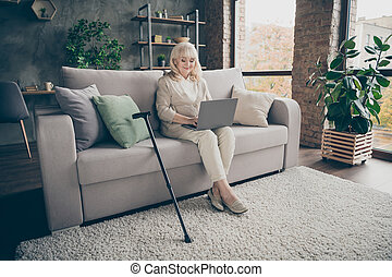 Portrait of her she nice attractive kind peaceful friendly gray-haired lady sitting on divan sending email to relatives inviting to visit at industrial brick loft modern style interior house indoors
