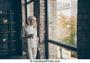 Portrait of her she nice attractive lovely cheerful dreamy gray-haired blond middle aged granny looking at window resting drinking cacao at industrial brick loft modern style interior house apartment