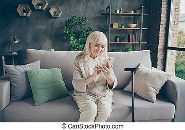 Portrait of her she nice attractive lovely cheery cheerful gray-haired grandma sitting on divan typing sms to relatives retirement at industrial brick loft modern style interior house