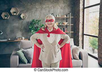Portrait of her she nice attractive strong powerful cheerful cheery glad gray-haired lady wearing red costume super granny at industrial brick loft modern style interior house