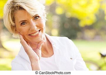 portrait of lovely middle aged woman sitting at the park