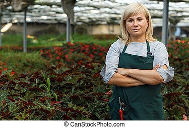Portrait of mature female gardener standing near begonia plants