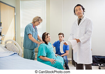 Portrait of mature male doctor explaining fetal heartbeat report to pregnant woman while nurse and man looking her in hospital