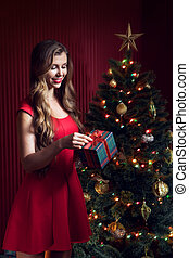 portrait of nice woman in red dress opening Christmas tree