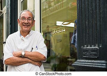 portrait of old barber smiling in hair salon