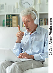 senior man at home with laptop