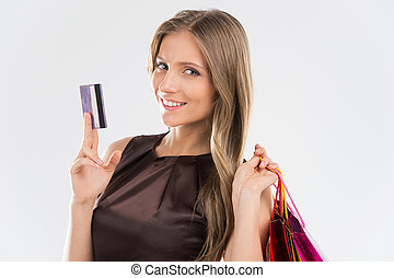 Portrait of young beautiful smiling woman with credit card. Brunette girl and many colorful shopping bags isolated on white background