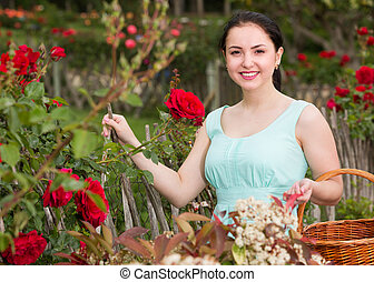 portrait of young female holding a basket near roses in outdoors