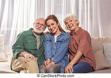 Positive grandparents with female locating on couch