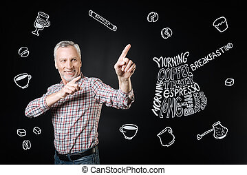 Positive owner of the cafe smiling and pointing to a new tasty coffee