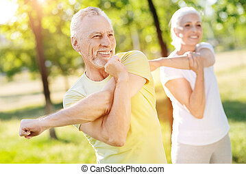 Positive retired couple stretching their hands